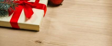 Indpakket julegave ligger under juletræ