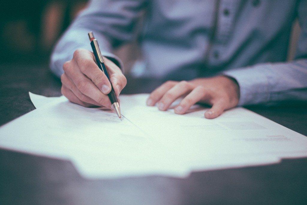 mand-underskriver-papirer-med-en-laekker-kuglepen-kontrakt