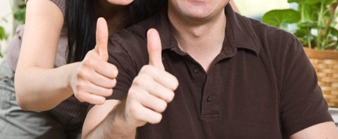 smilende ungt par giver thumbs up foran computer